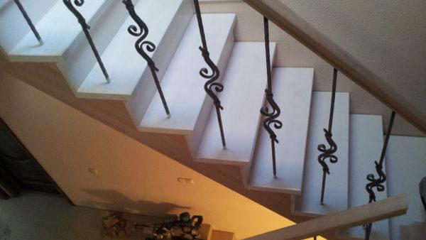 Лестница на металлическом каркасе обшита буком  с кованными ограждениями