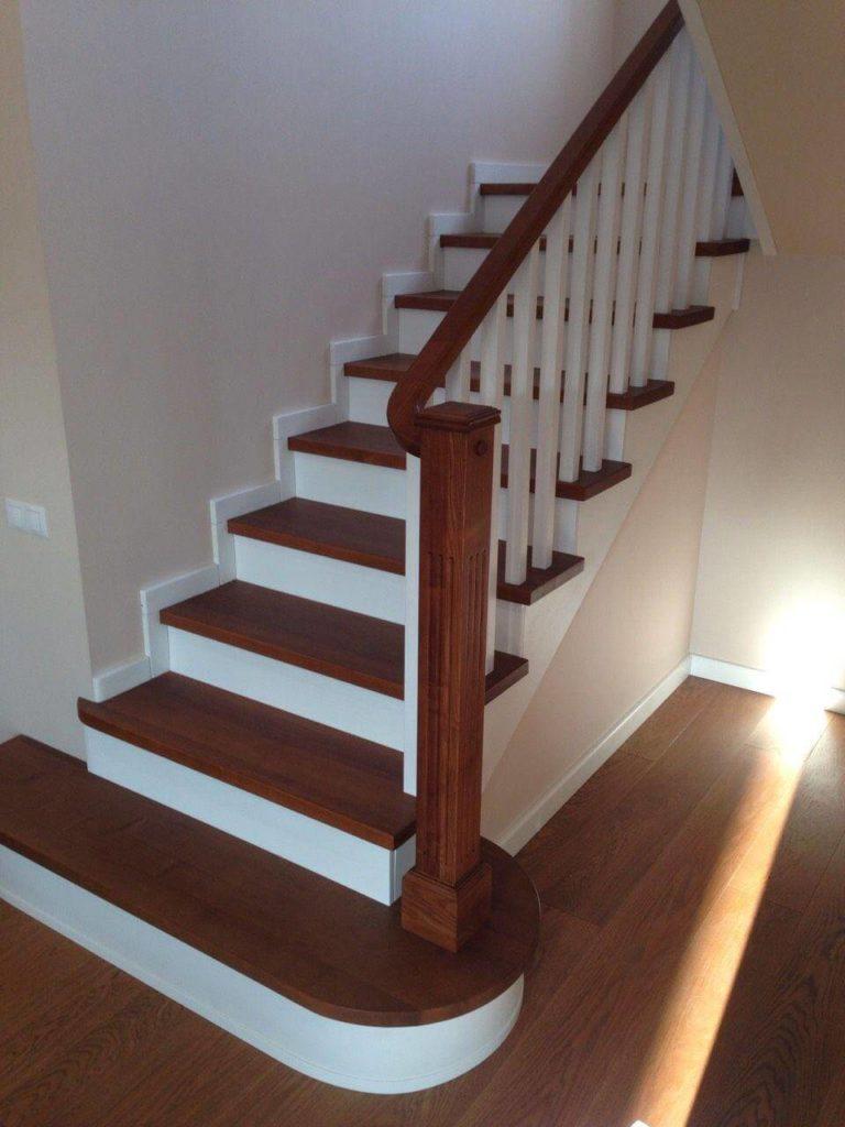 фотография лестницы на деревянных косоурах с белыми подступенями