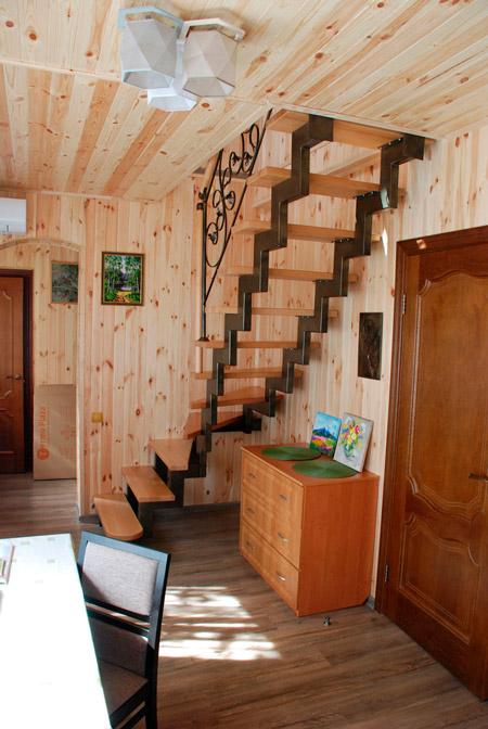фото деревянной лестницы на металлическом каркасе с коваными перилами