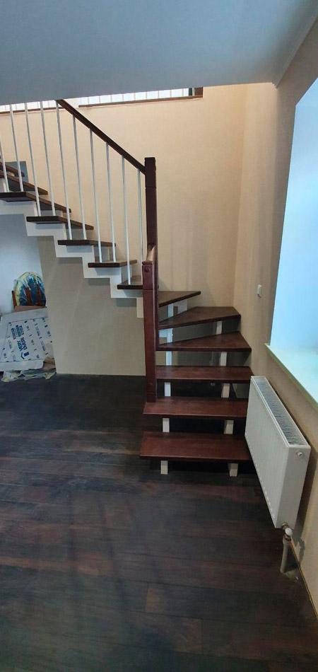 фотография деревянной лестницы на металлическом каркасе с поворотом с перилам из дерева