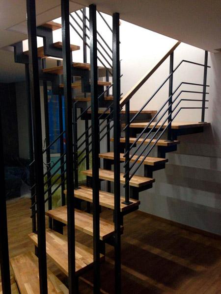 фото лестницы на металлическом каркасе с поворотом и перилами из дерева