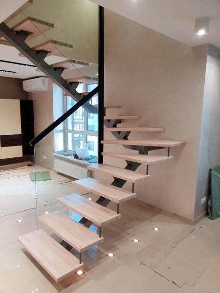 фото поворотной деревянной лестницы на металлическом каркасе с перилами из стекла
