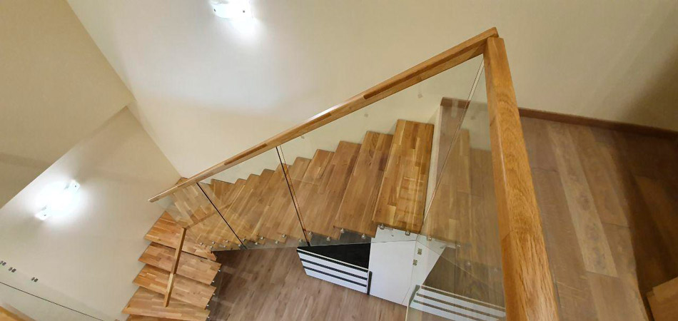 фото деревянной лестницы с поворотом на металлическом каркасе с перилами из стекла