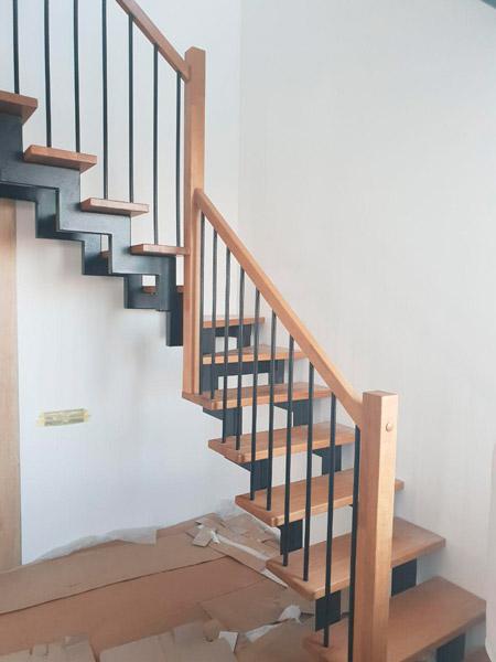 фото деревянной лестницы на металлическом каркасе с перилами и поворотом