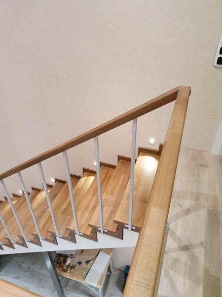 фото поворотной деревянной лестницы с перилами из металла